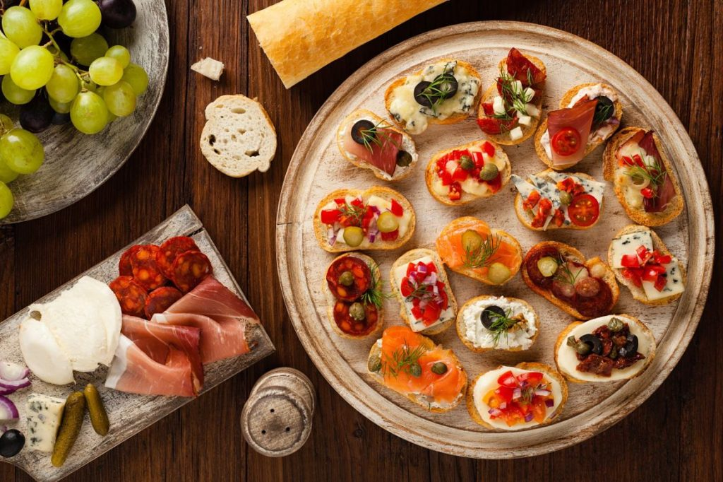 Crostini with different toppings on wooden background. Delicious appetizers. Top view.; Shutterstock ID 556329820; ISBN: 9782013960939; Titre: Blog article Toscane; Date: 16/01/2017